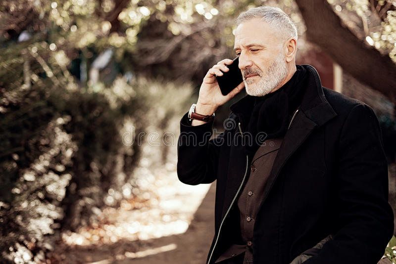 Hombre de negocios atractivo de la Edad Media que llama smartphone mientras que pasa tiempo en un parque urbano Fondo horizontal, fotografía de archivo libre de regalías