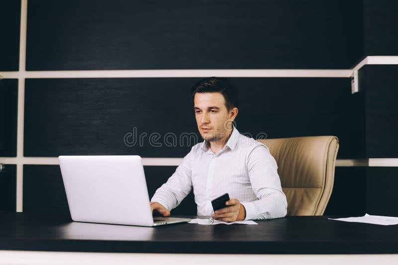 Hombre de negocios atractivo en la ropa de sport elegante que se sienta en su lugar de trabajo en oficina imágenes de archivo libres de regalías