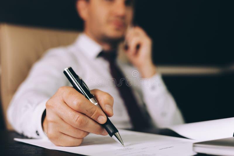 Hombre de negocios atractivo en la ropa de sport elegante que se sienta en su lugar de trabajo en la oficina que sostiene un telé imagenes de archivo
