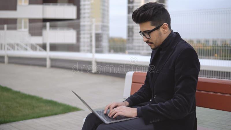 Hombre de negocios atractivo en traje negro usando el ordenador portátil que se sienta al aire libre fotografía de archivo