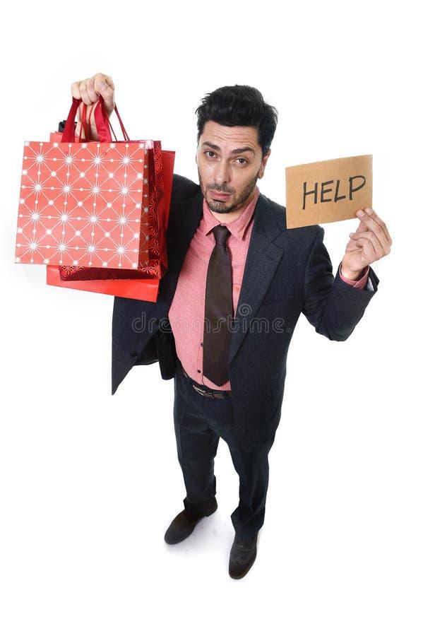Hombre de negocios atractivo joven en la tensión que sostiene la porción de panieres y muestra de la ayuda que mira haber agujere fotos de archivo libres de regalías