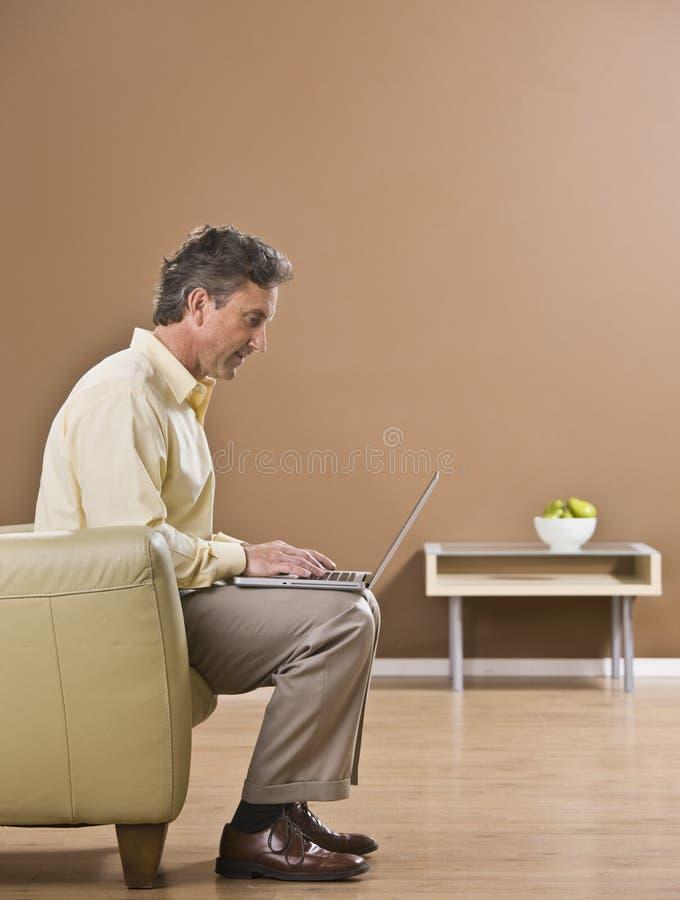 Hombre de negocios atractivo que usa la computadora portátil imagen de archivo