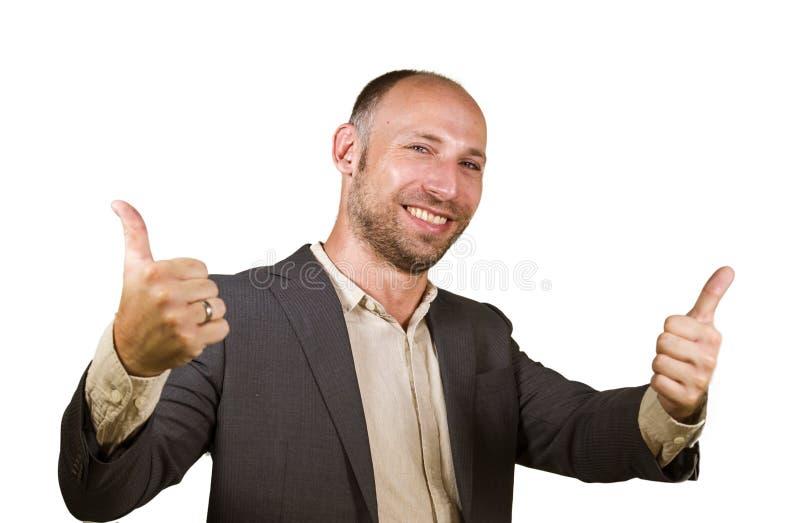 Hombre de negocios atractivo y acertado joven que sonríe fondo blanco aislado feliz y confiado que da el pulgar para arriba en em fotografía de archivo libre de regalías