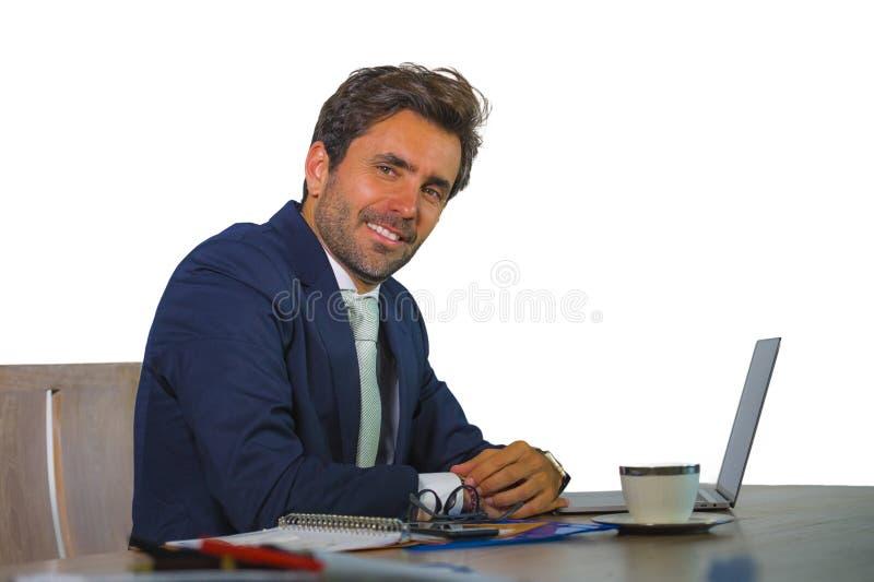 Hombre de negocios atractivo y eficiente joven que trabaja en el escritorio del ordenador portátil de la oficina confiado en la s imagen de archivo libre de regalías