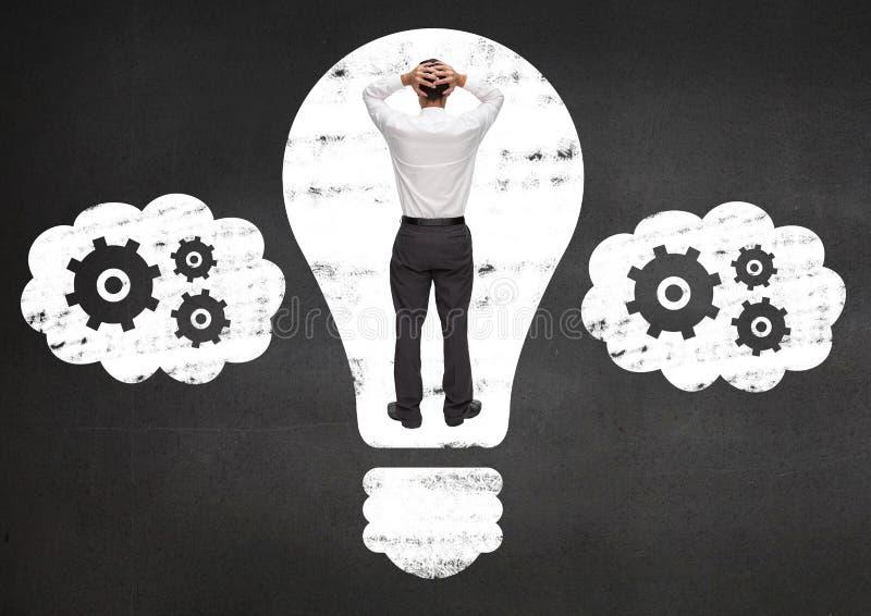 Hombre de negocios atrapado en bulbo eléctrico contra fondo negro imagen de archivo