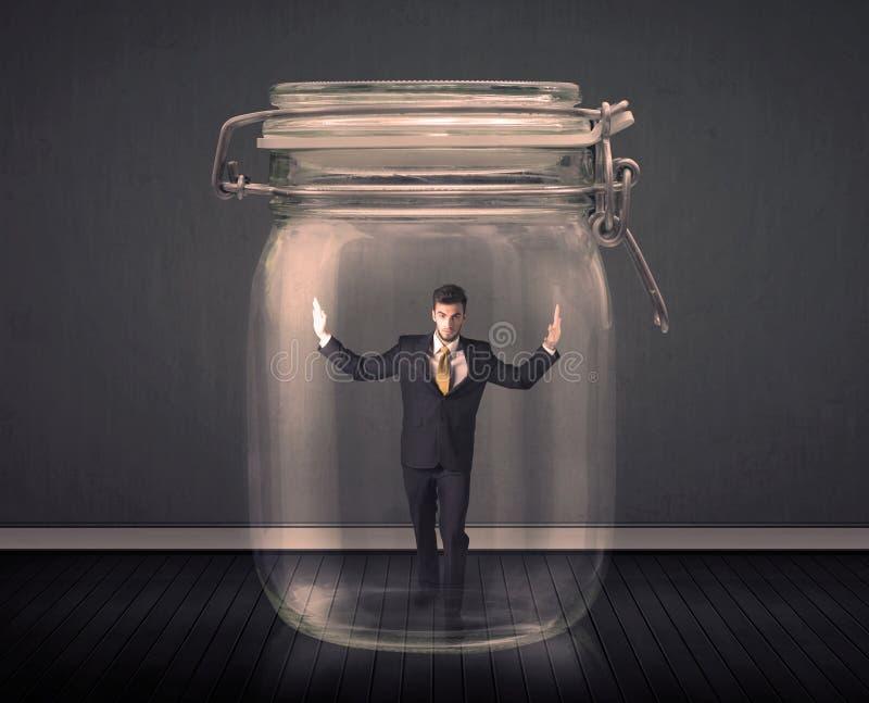 Hombre de negocios atrapado en un concepto de cristal del tarro foto de archivo