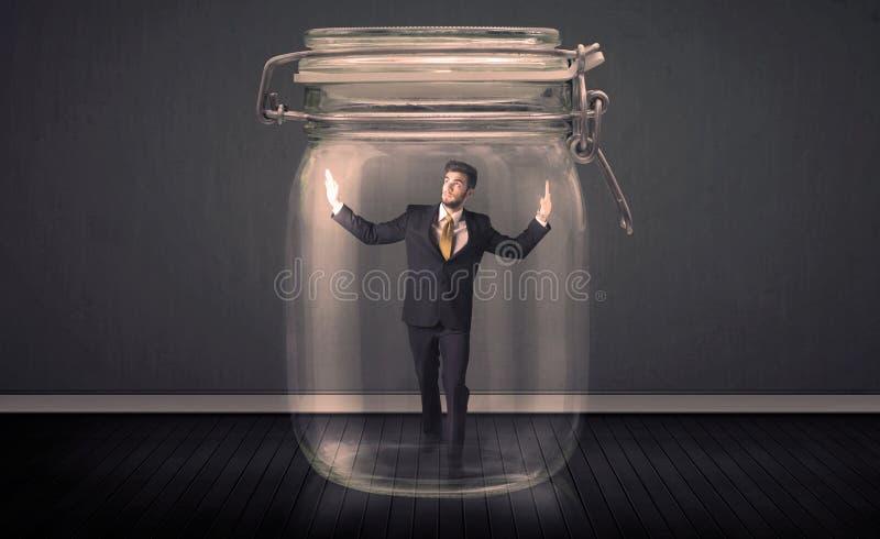 Hombre de negocios atrapado en un concepto de cristal del tarro imagen de archivo