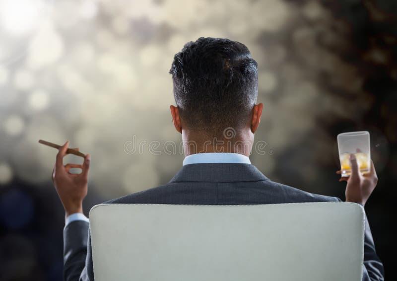 Hombre de negocios Back Sitting en silla con el cigarro y el vidrio de la bebida con las luces chispeantes del bokeh imágenes de archivo libres de regalías