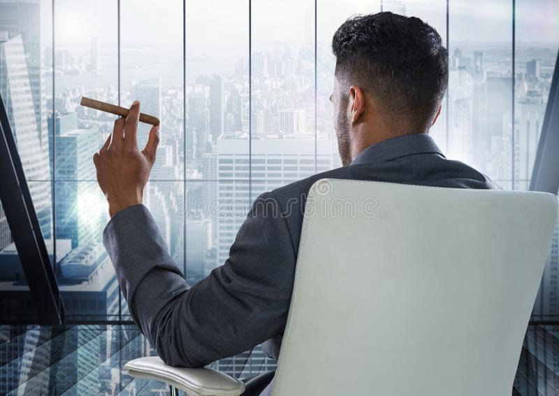 Hombre de negocios Back Sitting en silla pulida con el cigarro y la ventana que pasan por alto la ciudad moderna foto de archivo
