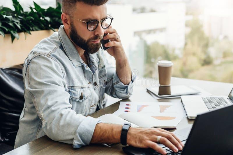 Hombre de negocios barbudo, blogger que se sienta en café, hablando en el teléfono elegante, trabajando en el ordenador portátil, fotografía de archivo