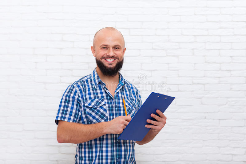 Hombre de negocios barbudo casual que lleva a cabo el documento del lápiz de la carpeta que escribe sonrisa feliz fotos de archivo