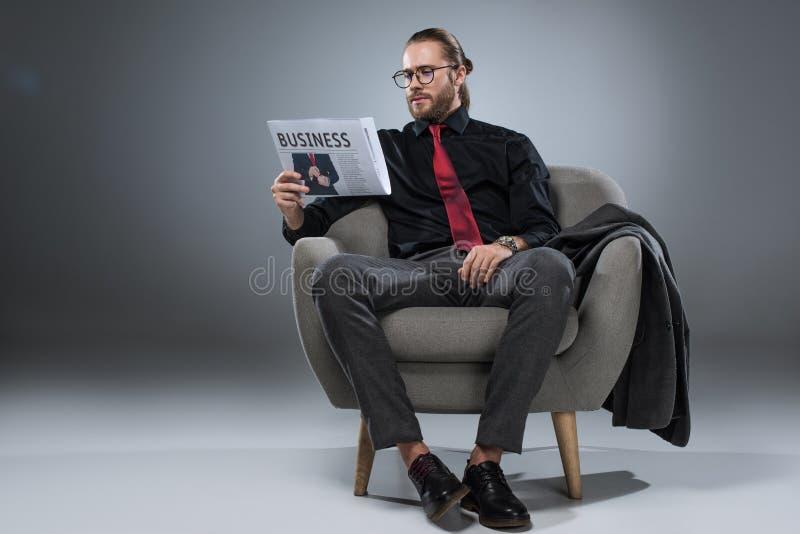 Hombre de negocios barbudo caucásico en los vidrios que se sientan en butaca y que leen el periódico, imagen de archivo