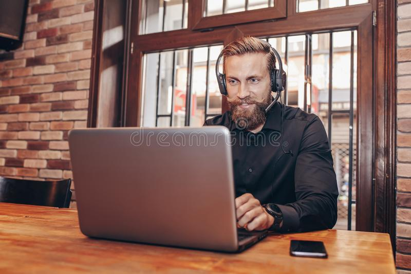 Hombre de negocios barbudo con el funcionamiento de las auriculares con el ordenador portátil fotos de archivo