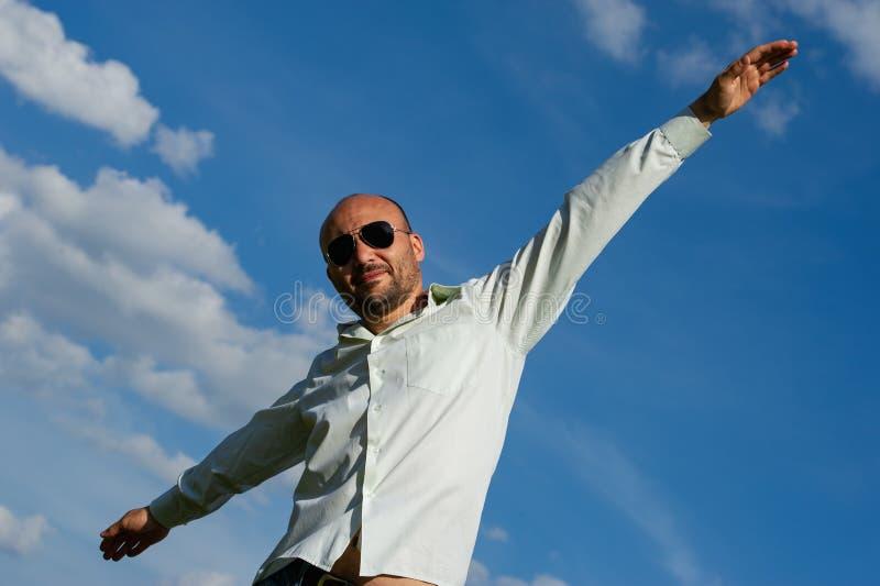 Hombre de negocios barbudo con las gafas de sol que estiran sus brazos contra foto de archivo