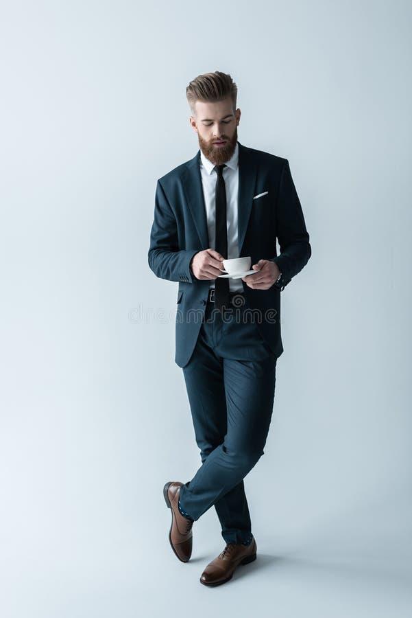 Hombre de negocios barbudo en el traje elegante que sostiene la taza de café en gris imagenes de archivo