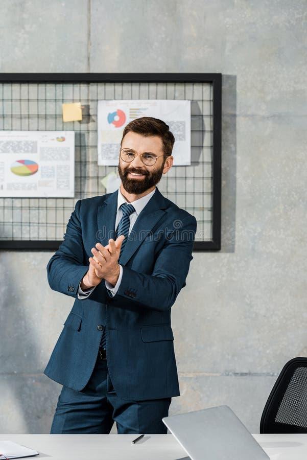 hombre de negocios barbudo feliz que aplaude y que sonríe en la cámara fotografía de archivo libre de regalías