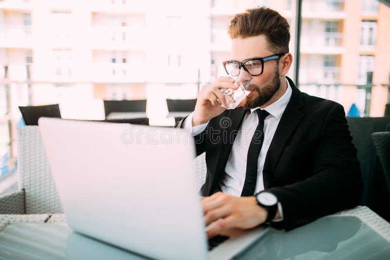 Hombre de negocios barbudo feliz que se sienta por la taza de la bebida de la tabla de café y que usa el ordenador portátil en ca fotos de archivo
