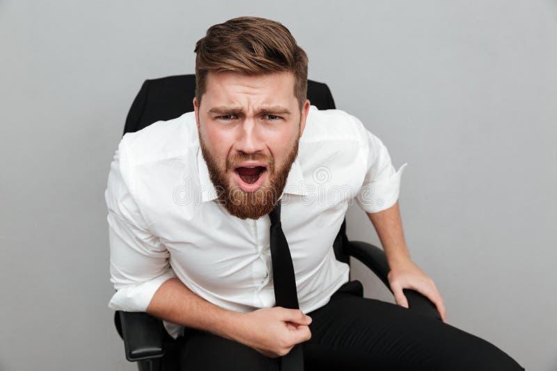 Hombre de negocios barbudo frustrado que se sienta en silla y que mira fijamente la cámara imágenes de archivo libres de regalías