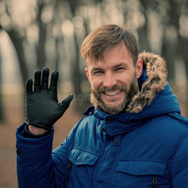Hombre de negocios barbudo Gestures Greetingily Hombre barbudo Mirada En el parque de la ciudad fotos de archivo