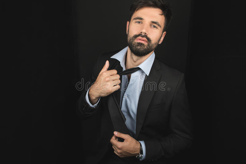 Hombre de negocios barbudo hermoso que presenta en lazo y traje negro imagen de archivo libre de regalías