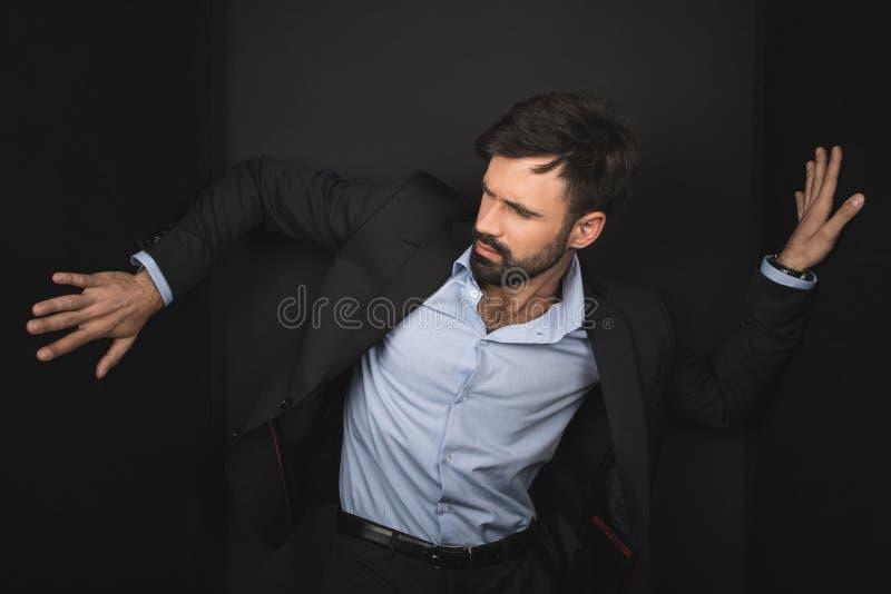 Hombre de negocios barbudo hermoso que presenta en traje negro imagenes de archivo