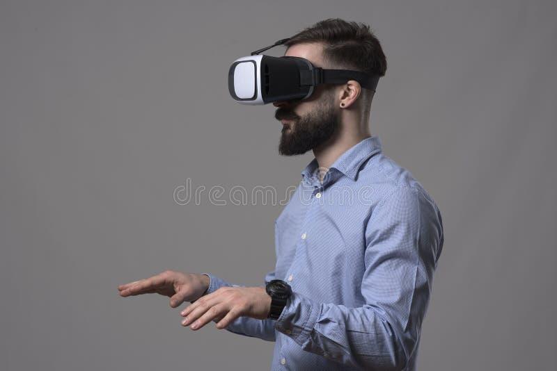 Hombre de negocios barbudo joven con los vidrios del vr que mecanografía en el simulador aumentado del teclado de la realidad foto de archivo libre de regalías