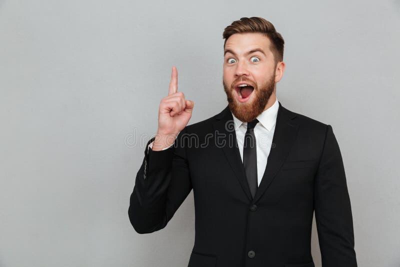 Hombre de negocios barbudo joven emocionado que tiene una idea imagen de archivo