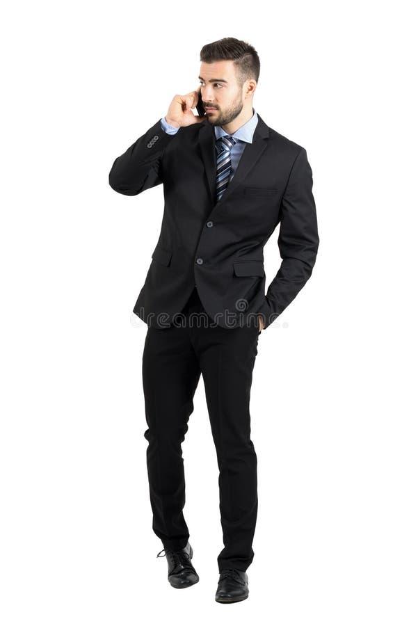 Hombre de negocios barbudo joven en traje que habla en el teléfono que camina hacia la cámara que mira lejos foto de archivo