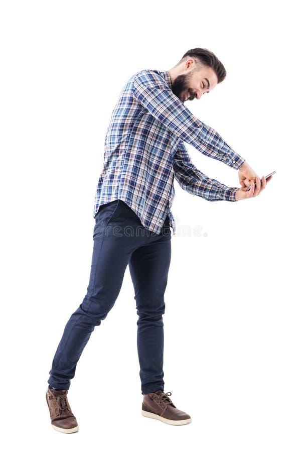 Hombre de negocios barbudo joven furioso que perfora la exhibición del teléfono móvil con el puño foto de archivo libre de regalías