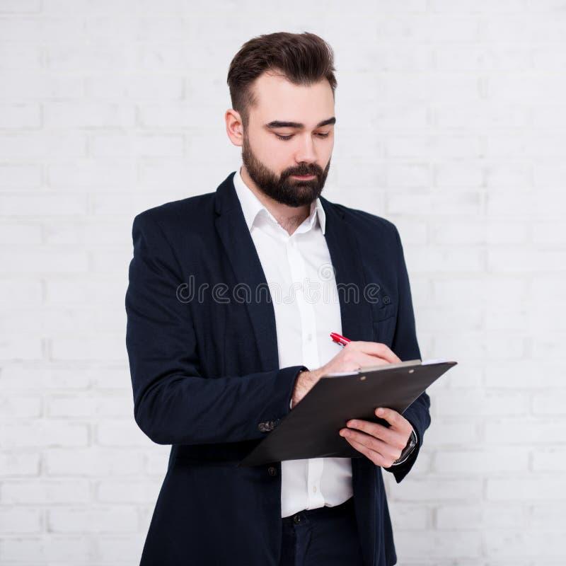 Hombre de negocios barbudo joven que escribe algo en el tablero sobre la pared de ladrillo blanca fotos de archivo libres de regalías