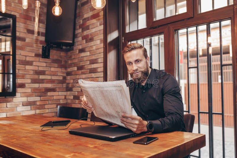 Hombre de negocios barbudo joven que lee un periódico imagenes de archivo