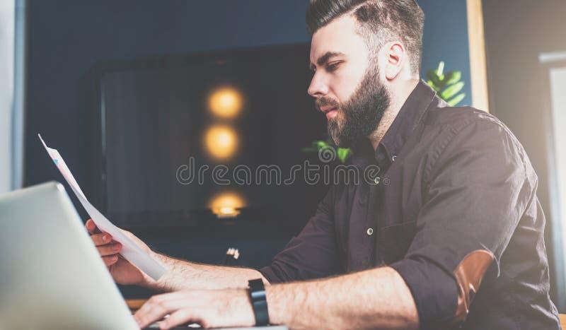 Hombre de negocios barbudo joven que se sienta en oficina en la tabla, leyendo documentos y trabajando en el ordenador portátil H fotografía de archivo libre de regalías