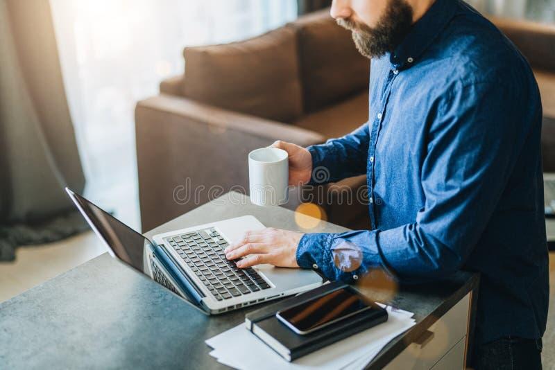 Hombre de negocios barbudo joven que trabaja en el ordenador en la tabla, café de consumición El hombre analiza la información, d fotografía de archivo