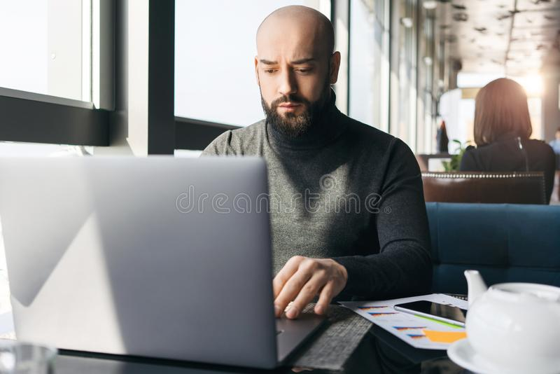 Hombre de negocios barbudo joven que trabaja en el ordenador portátil mientras que se sienta en café El Freelancer trabaja remota foto de archivo libre de regalías