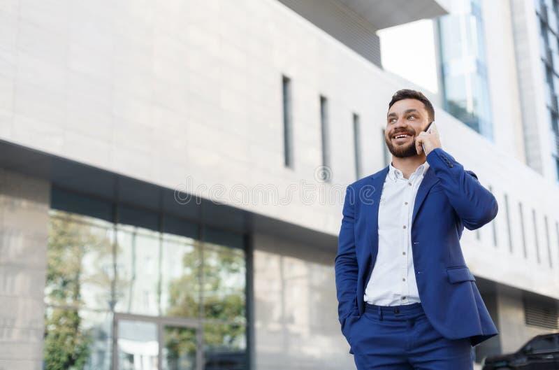 Hombre de negocios barbudo que habla en el teléfono celular con el cliente imagen de archivo