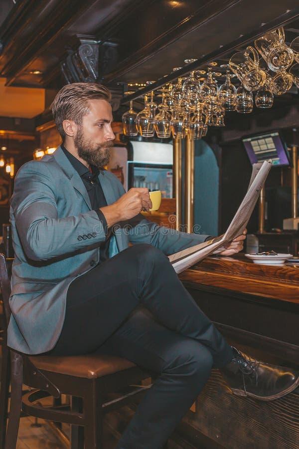 Hombre de negocios barbudo que lee un periódico fotos de archivo libres de regalías