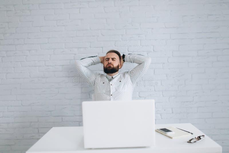Hombre de negocios barbudo que se sienta en el escritorio en oficina y la relajación fotografía de archivo libre de regalías