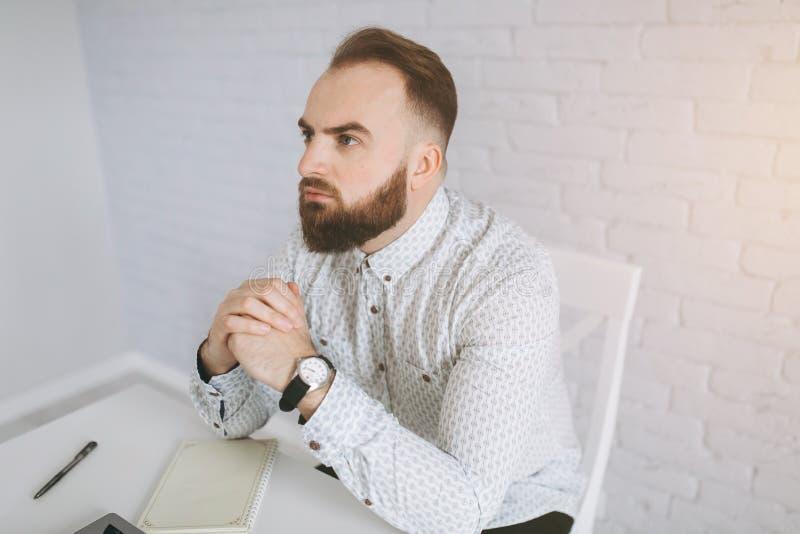 Hombre de negocios barbudo que se sienta en un escritorio en la oficina imagen de archivo