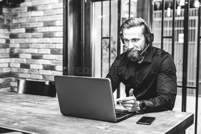 Hombre de negocios barbudo que tiene una llamada video con un ordenador portátil imágenes de archivo libres de regalías