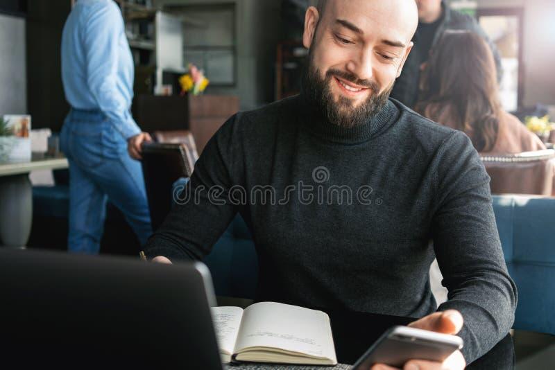 Hombre de negocios barbudo que trabaja en el ordenador portátil mientras que se sienta en café, usando el smartphone, haciendo en imagen de archivo libre de regalías