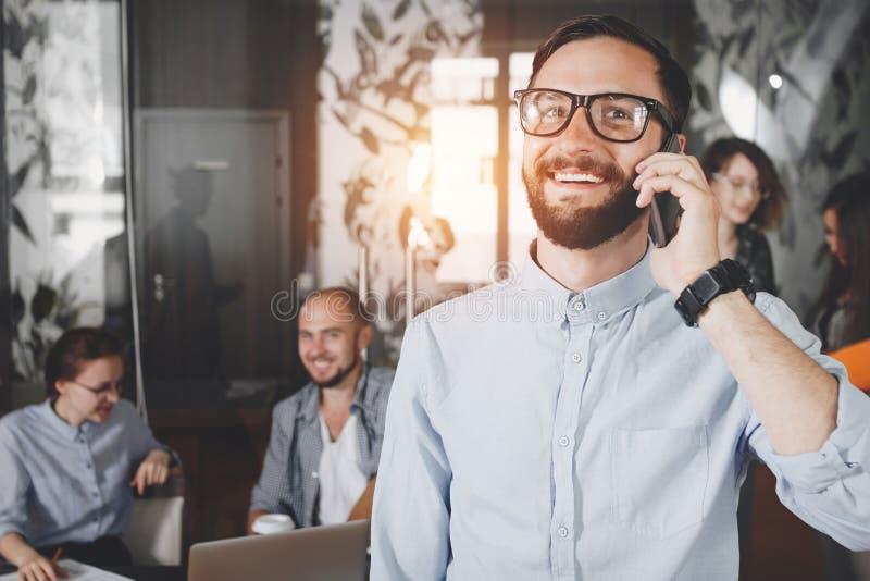 Hombre de negocios barbudo sonriente de los jóvenes del primer de la foto en spea de los vidrios imagen de archivo