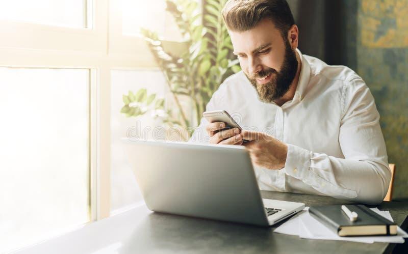 Hombre de negocios barbudo sonriente de los jóvenes que se sienta en la tabla delante del ordenador, usando smartphone Hombre que imagen de archivo libre de regalías