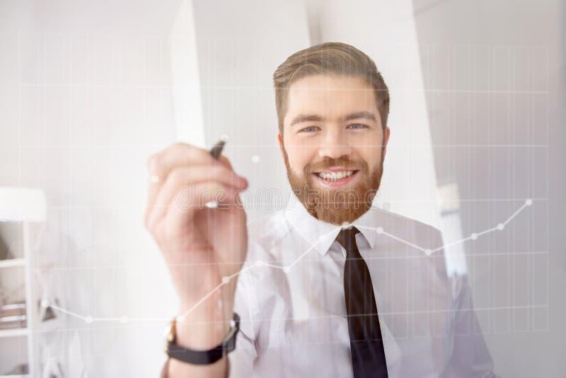 Hombre de negocios barbudo sonriente que trabaja con la pantalla futurista y los diagramas de dibujo imágenes de archivo libres de regalías