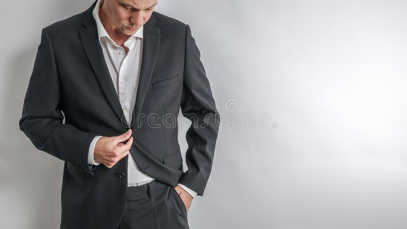 Hombre de negocios bien vestido en el traje negro que ajusta su chaqueta fotografía de archivo libre de regalías