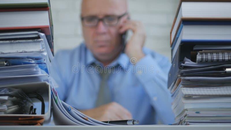 Hombre de negocios In Blurred Image que habla con el teléfono móvil en sitio del archivo imagen de archivo libre de regalías