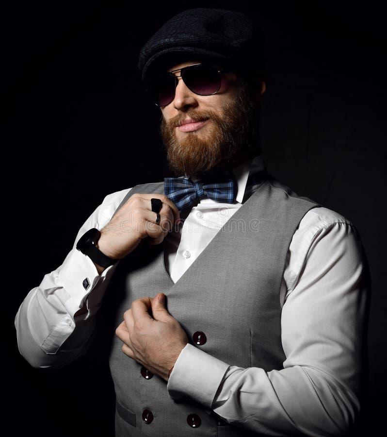 Hombre de negocios brutal con la barba y bigote en gafas de sol y chaqueta y corbata de lazo del desgaste del casquillo fotografía de archivo libre de regalías