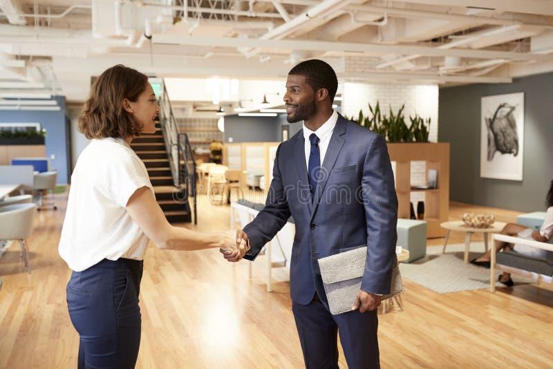 Hombre de negocios And Businesswoman Meeting y manos de la sacudida en oficina abierta moderna del plan foto de archivo