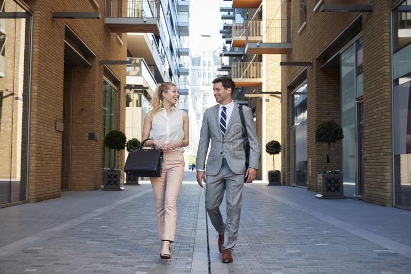 Hombre de negocios And Businesswoman Walk a trabajar a través de la calle de la ciudad foto de archivo libre de regalías