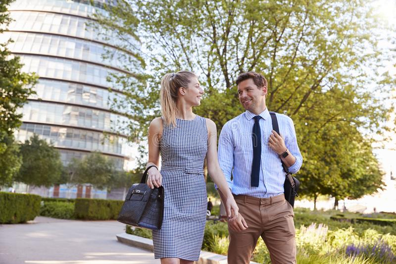 Hombre de negocios And Businesswoman Walk a trabajar a través de parque de la ciudad imágenes de archivo libres de regalías