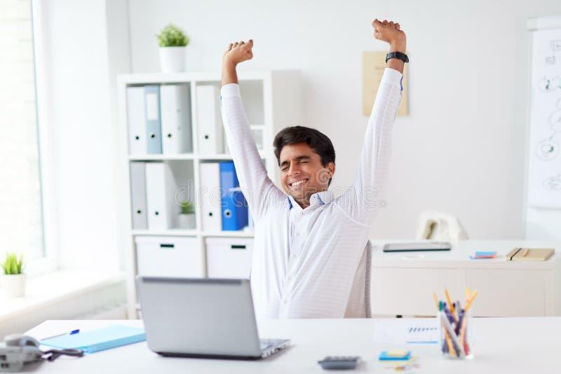 Hombre de negocios cansado con el ordenador portátil que estira en la oficina fotos de archivo